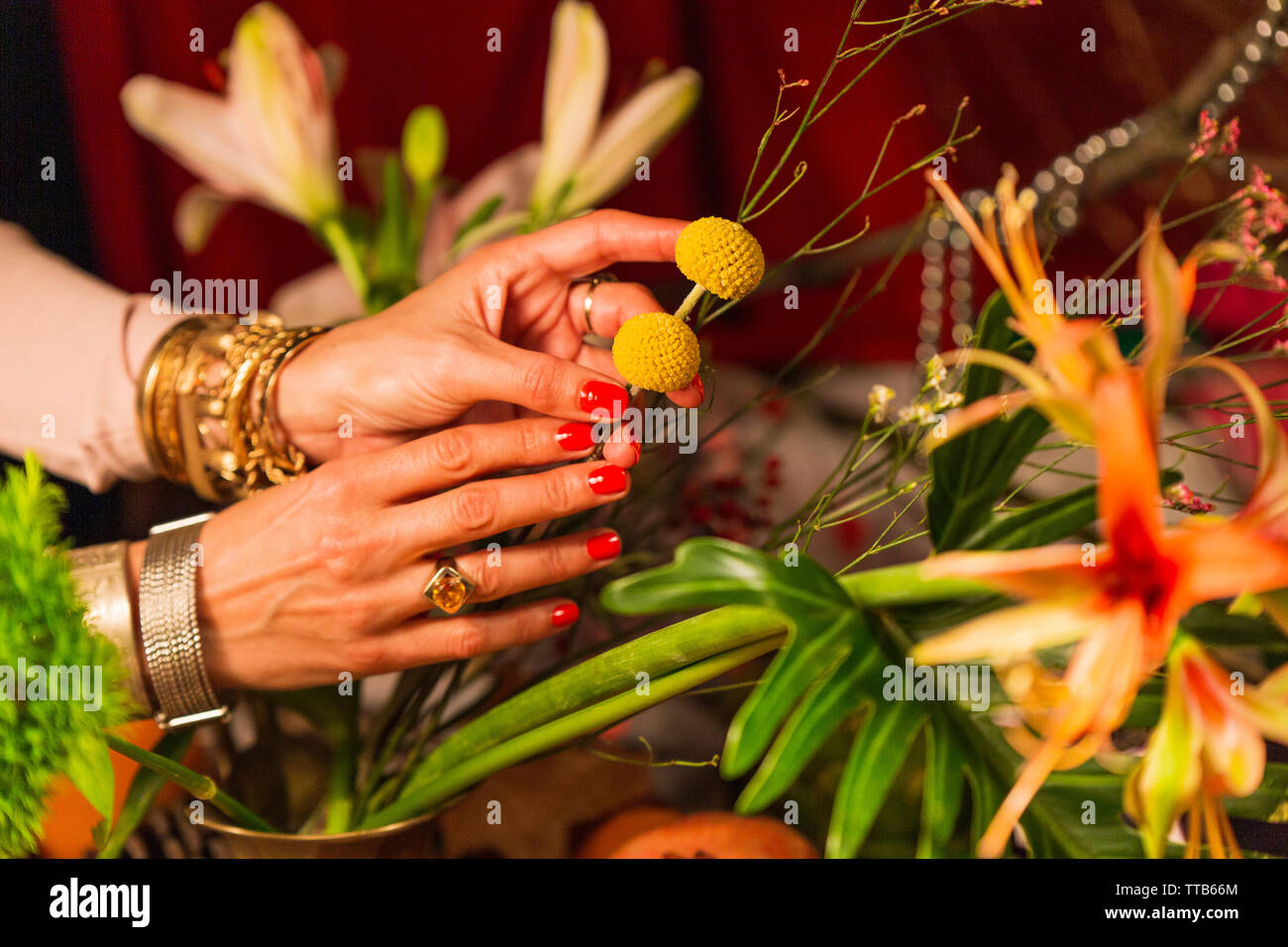 Hand holding flowers in front of autumn crops Stock Photo