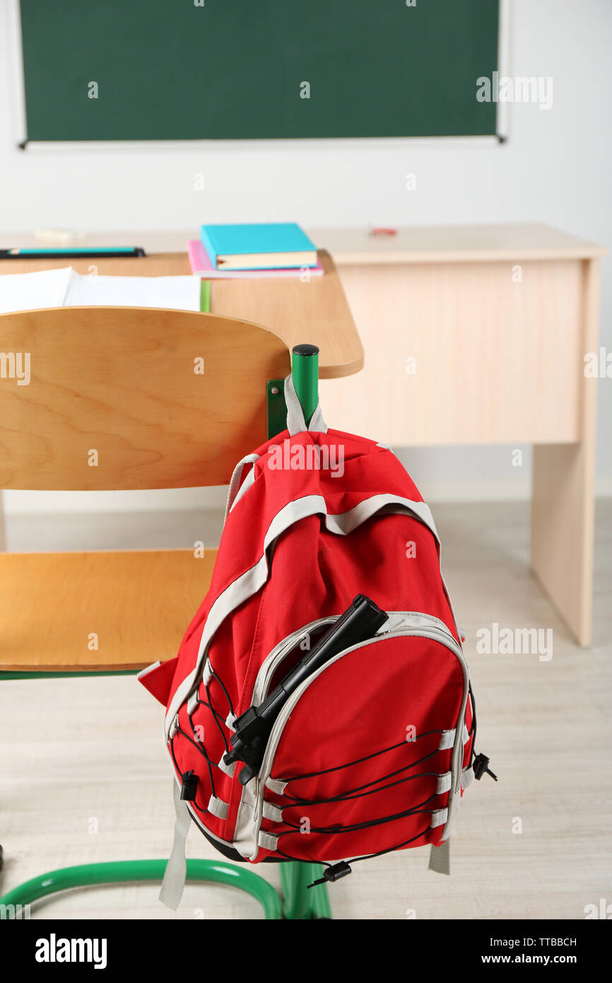 Backpack with gun in classroom, close up. Juvenile delinquency Stock Photo