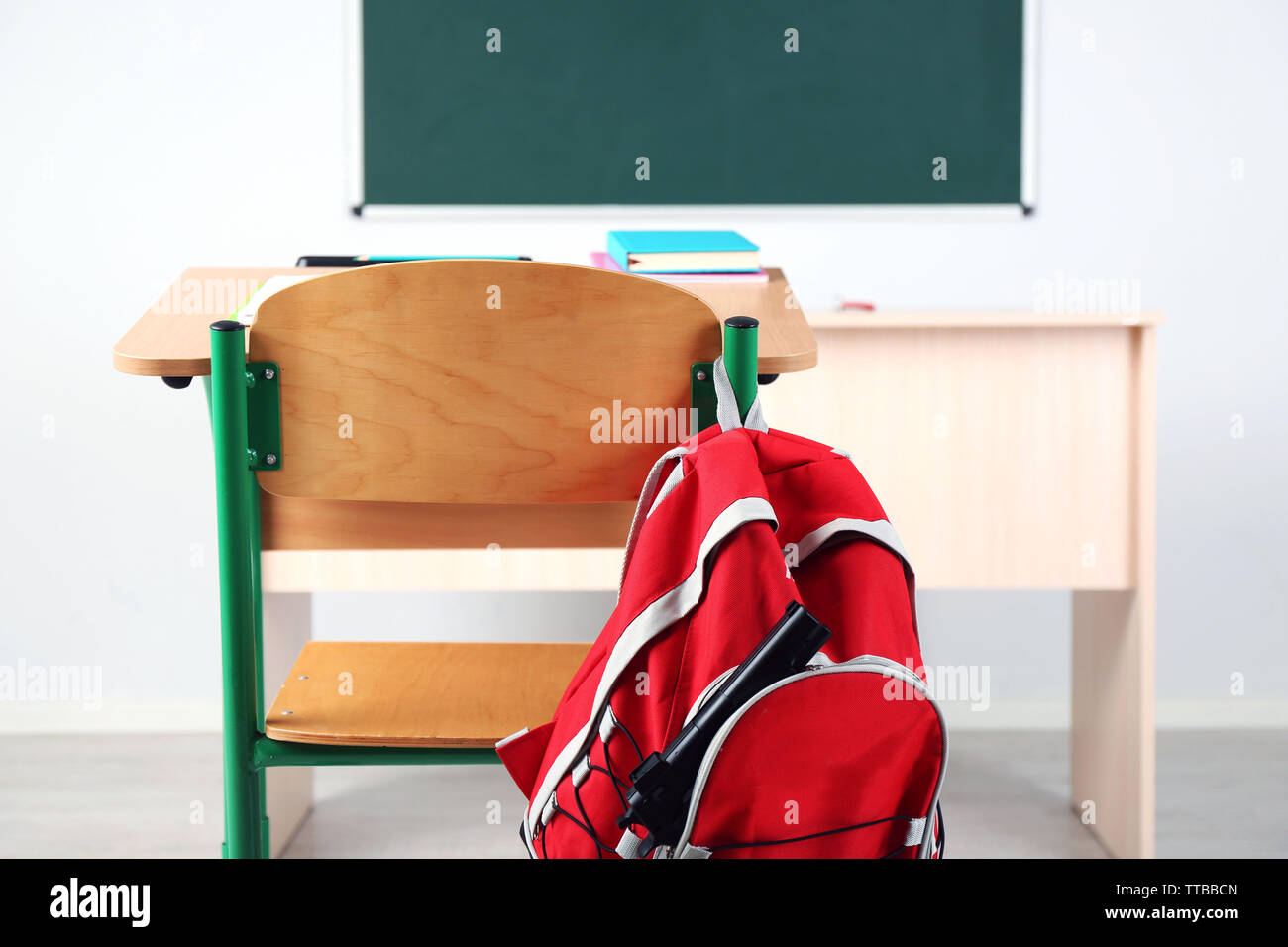 Backpack with gun in classroom, close up. Juvenile delinquency - Stock Image
