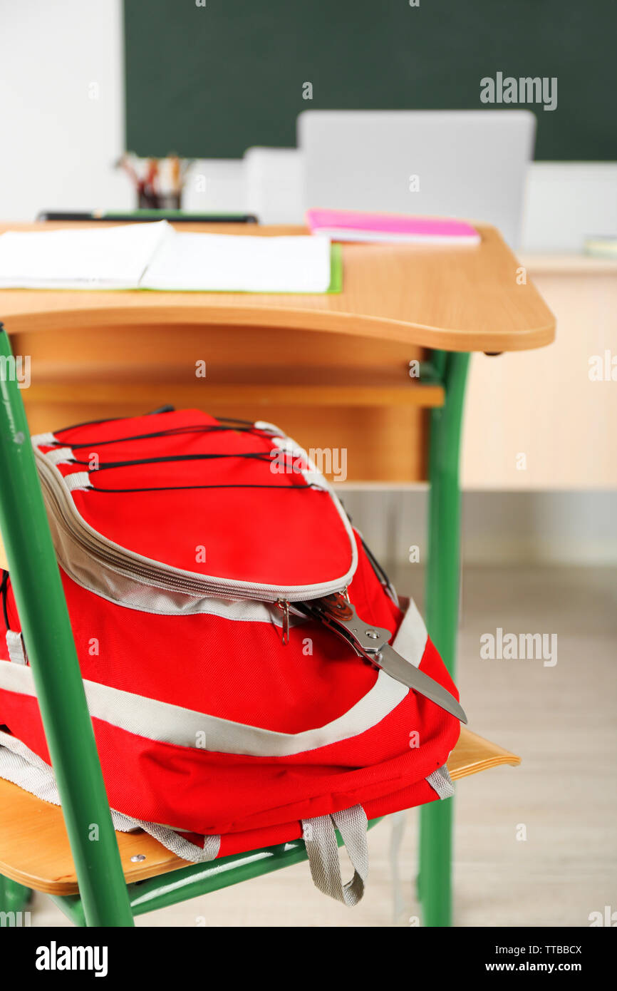 Backpack with knife in classroom, close up. Juvenile delinquency - Stock Image