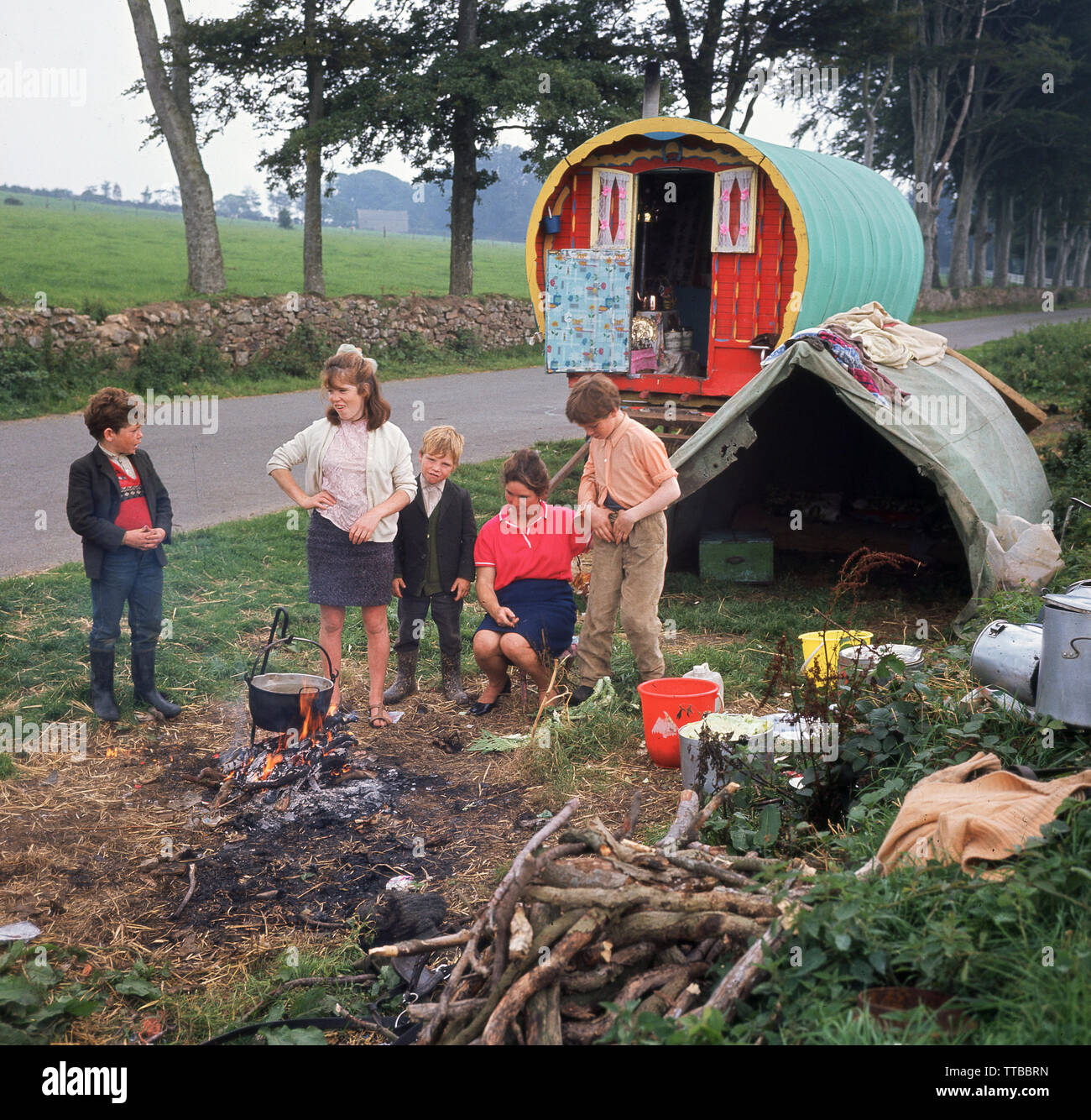 1960s, historical, Irish travellers... daytime and beside a country road in rural Ireland, a mother with her children cooking a pot on a fire outside  their home, a traditional barrel-roofed or bow top horse-drawn gypsy wagon and old tent. - Stock Image