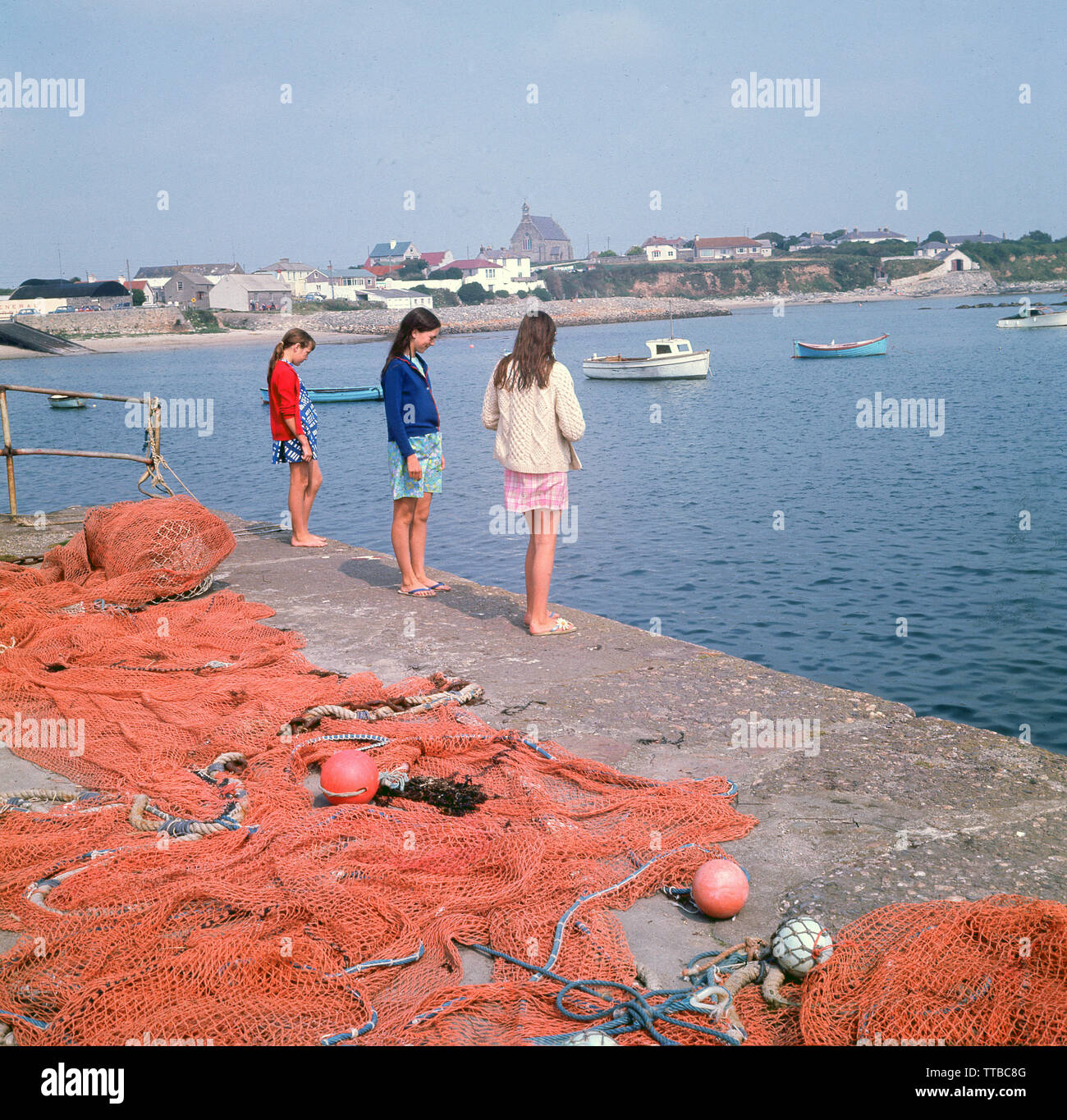 1960s, historical, three young teenage girls standing by fishing nets at the water's edge at the harbour in Kilmore, a fishing village in County Wexford, Ireland. - Stock Image