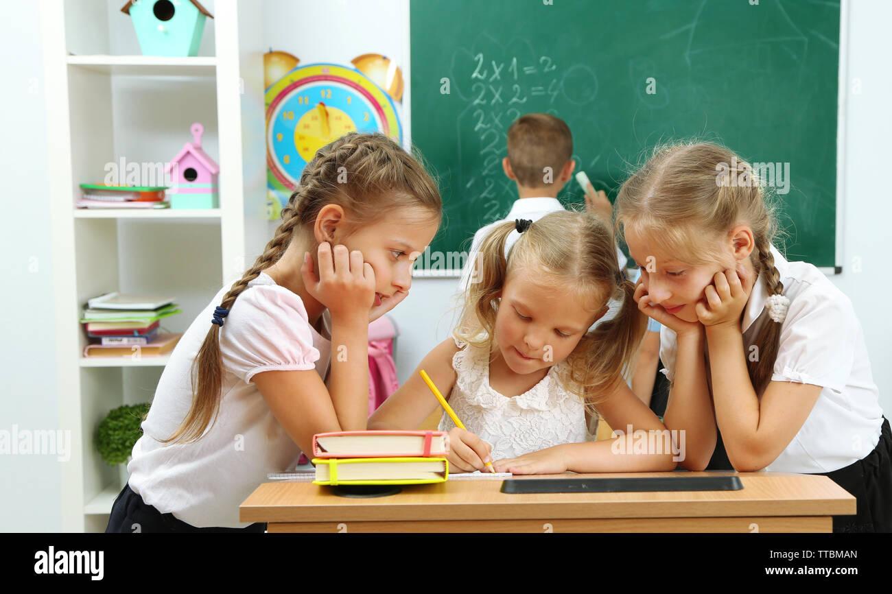 Portrait of happy schoolgirls at lesson - Stock Image