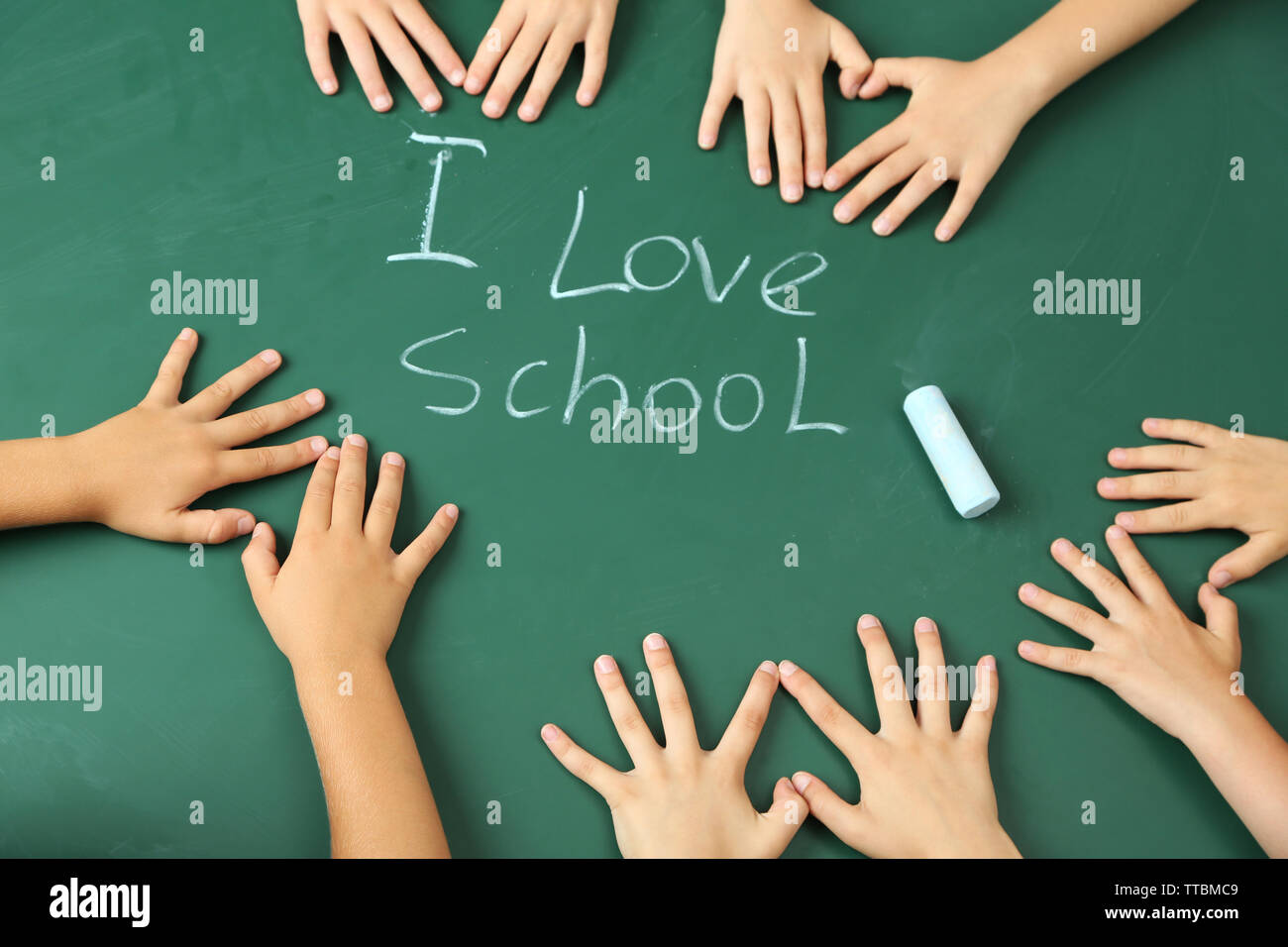 Children hands on blackboard background - Stock Image