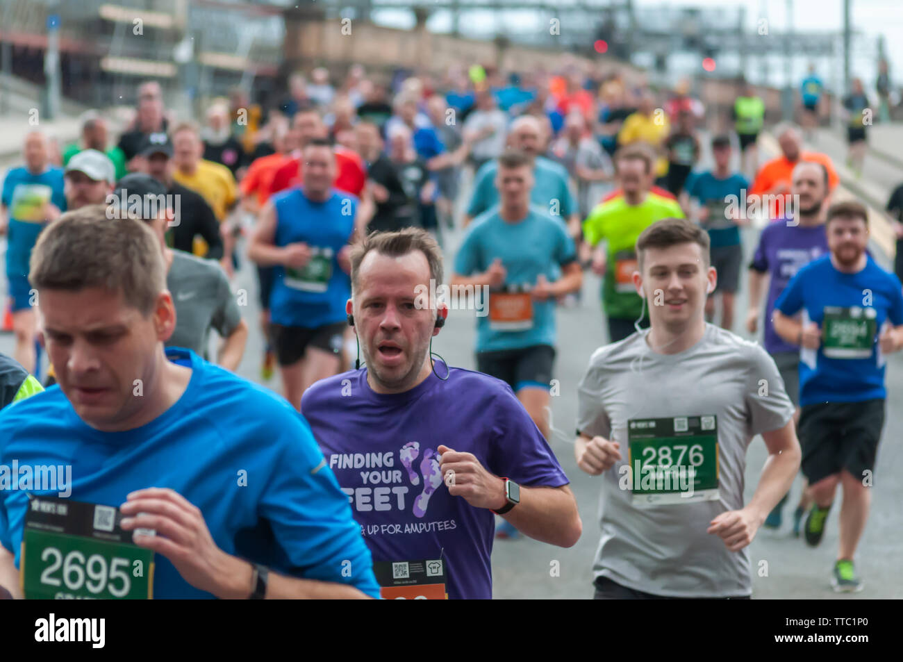 Glasgow, Scotland, UK. 16th June, 2019. Runners crossing the King George V Bridge during the Men's 10K Run which has been an annual event since 2004. Thousands of runners take to the streets of the city to get fit, fundraise, and raise awareness of men's health issues. The run coincides with Fathers Day and starts at the Riverside Museum and  finishes at George Square. Credit: Skully/Alamy Live News - Stock Image