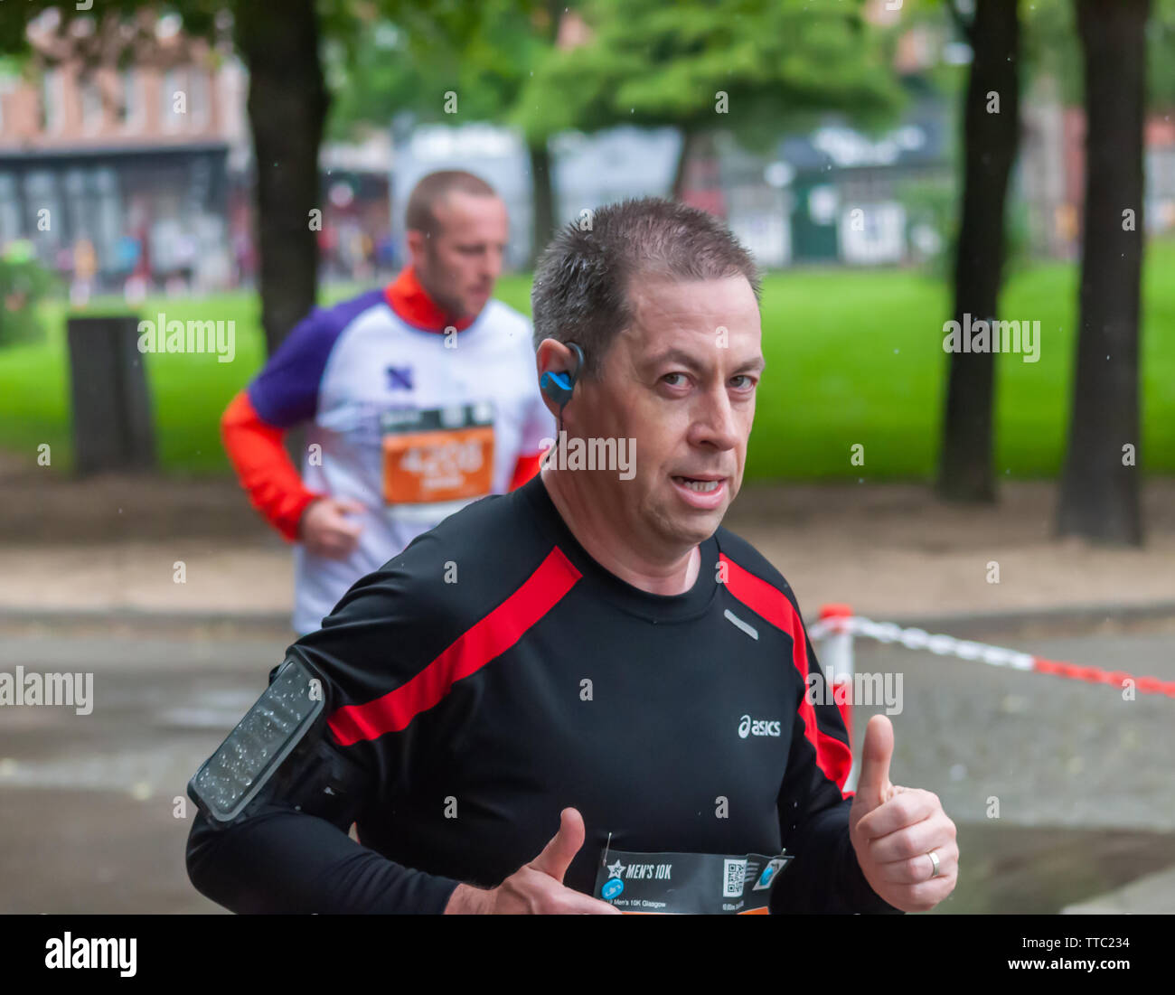 Glasgow, Scotland, UK. 16th June, 2019. Runners enter Glasgow Green during the Men's 10K Run which has been an annual event since 2004. Thousands of runners take to the streets of the city to get fit, fundraise, and raise awareness of men's health issues. The run coincides with Fathers Day and starts at the Riverside Museum and  finishes at George Square. Credit: Skully/Alamy Live News - Stock Image