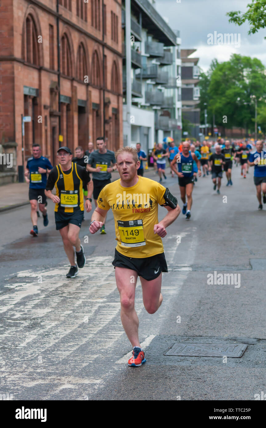 Glasgow, Scotland, UK. 16th June, 2019. Runners on Greendyke Street during the Men's 10K Run which has been an annual event since 2004. Thousands of runners take to the streets of the city to get fit, fundraise, and raise awareness of men's health issues. The run coincides with Fathers Day and starts at the Riverside Museum and  finishes at George Square. Credit: Skully/Alamy Live News - Stock Image