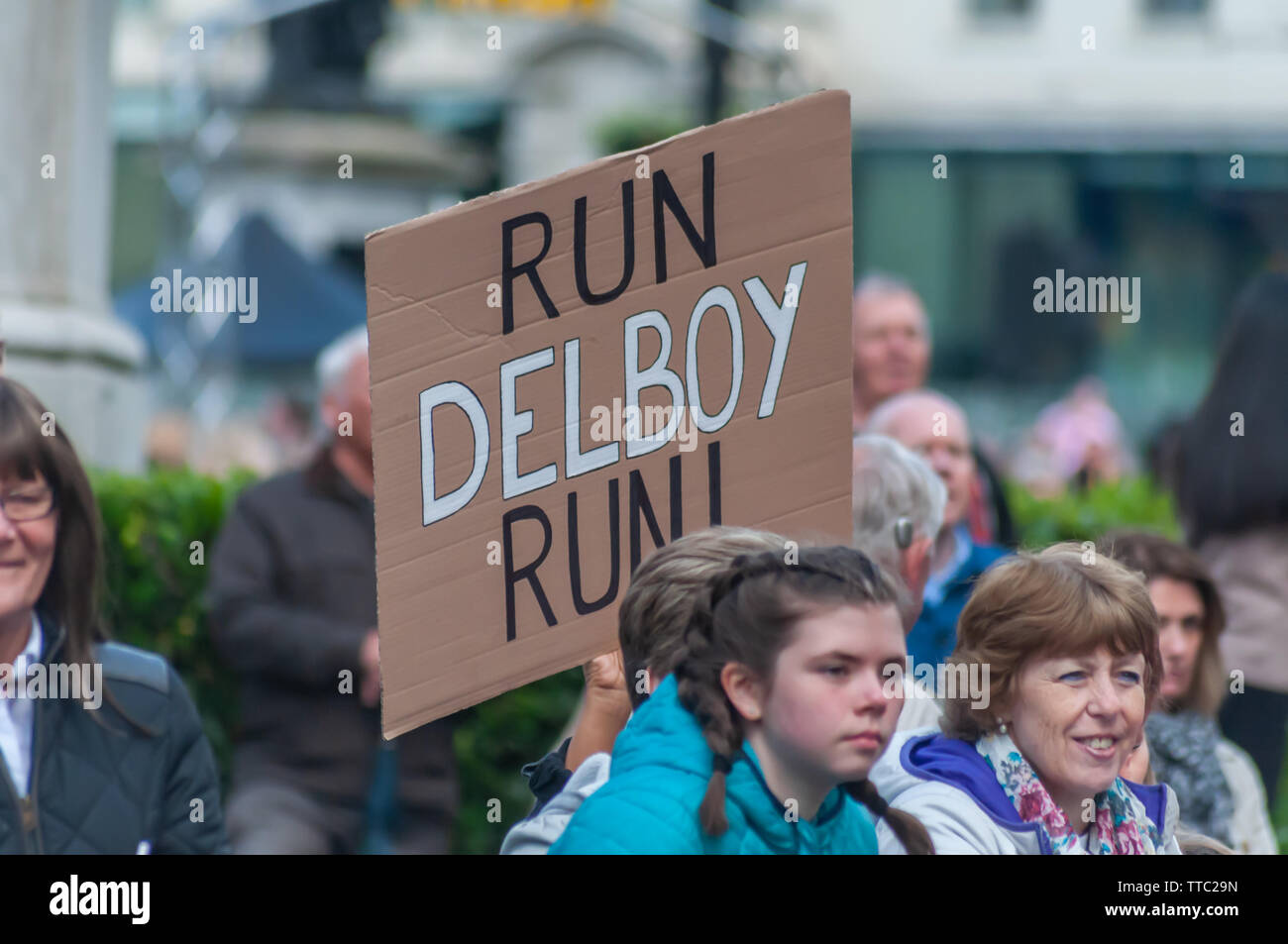 Glasgow, Scotland, UK. 16th June, 2019. Spectators in George Square holding a placard saying Run Delboy Run at the Men's 10K Run which has been an annual event since 2004. Thousands of runners take to the streets of the city to get fit, fundraise, and raise awareness of men's health issues. The run coincides with Fathers Day and starts at the Riverside Museum and  finishes at George Square. Credit: Skully/Alamy Live News - Stock Image