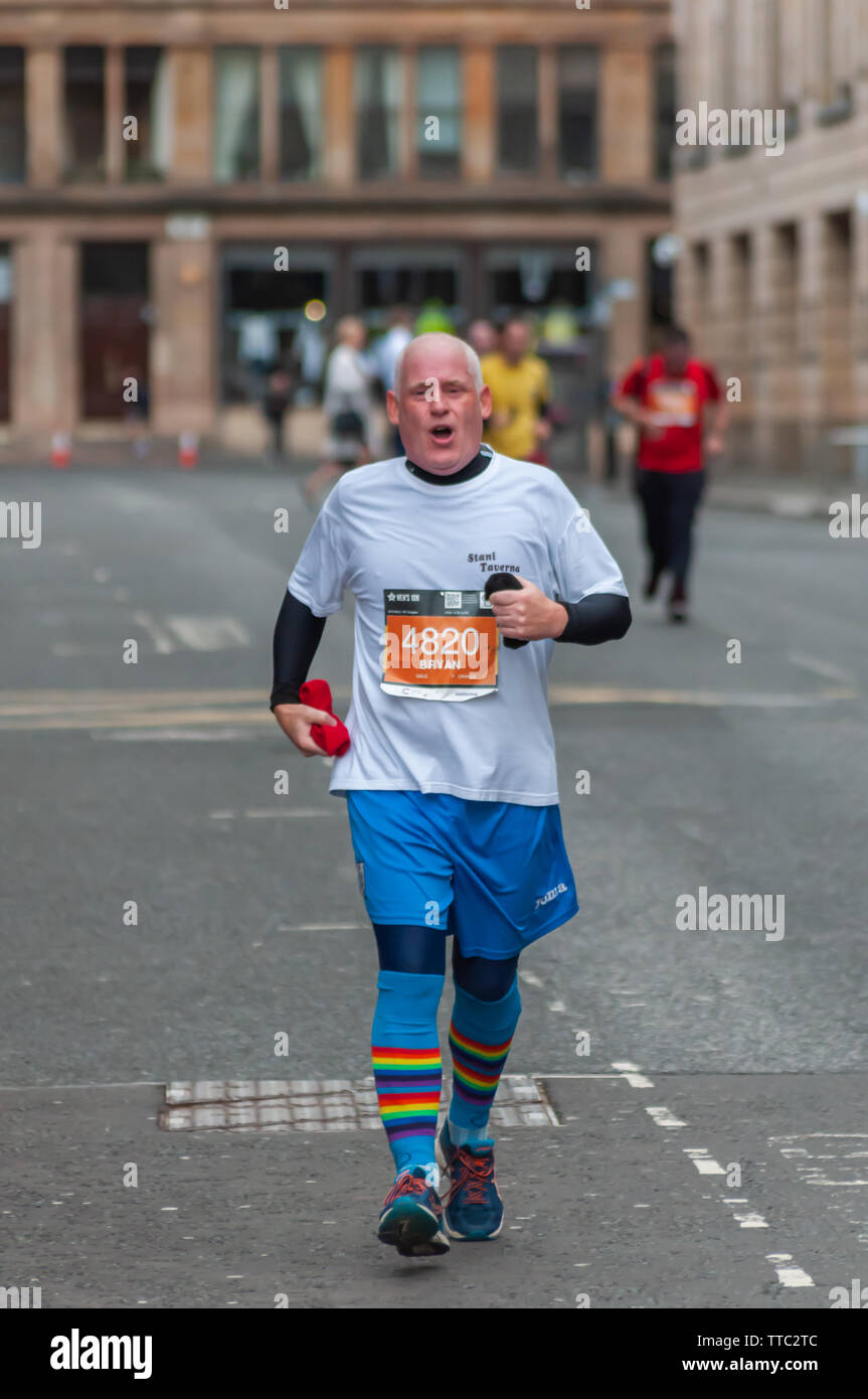 Glasgow, Scotland, UK. 16th June, 2019. A runner at Cochrane Street during the Men's 10K Run which has been an annual event since 2004. Thousands of runners take to the streets of the city to get fit, fundraise, and raise awareness of men's health issues. The run coincides with Fathers Day and starts at the Riverside Museum and  finishes at George Square. Credit: Skully/Alamy Live News - Stock Image