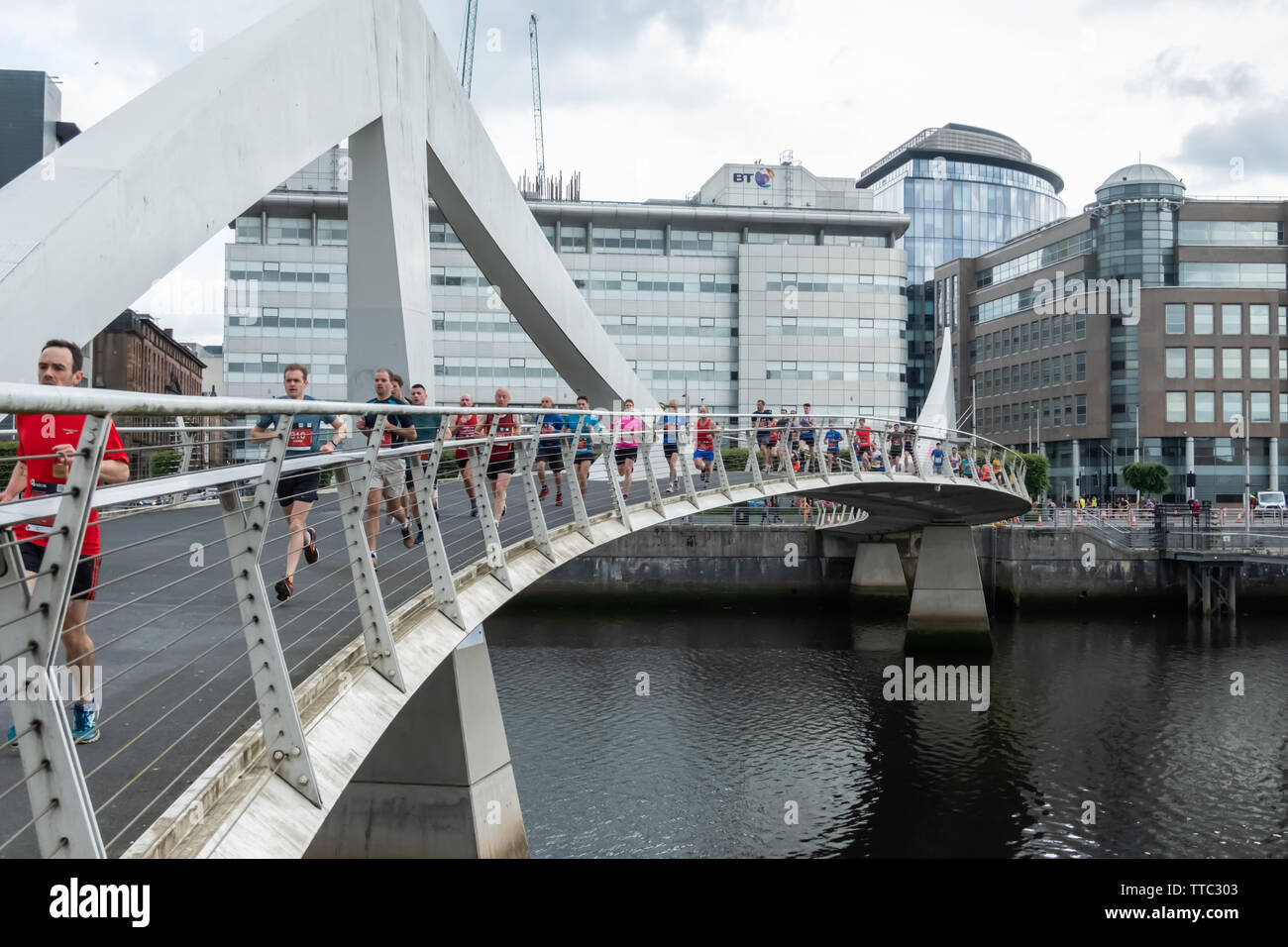 Glasgow, Scotland, UK. 16th June, 2019. Runners crossing the Tradeston Bridge during the Men's 10K Run which has been an annual event since 2004. Thousands of runners take to the streets of the city to get fit, fundraise, and raise awareness of men's health issues. The run coincides with Fathers Day and starts at the Riverside Museum and  finishes at George Square. Credit: Skully/Alamy Live News - Stock Image