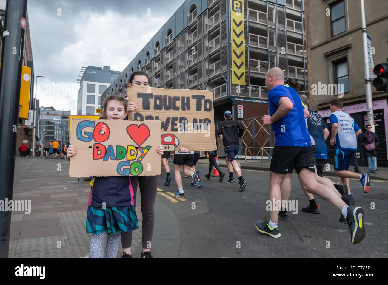 Glasgow, Scotland, UK. 16th June, 2019. Two girls holding placards that say Go Daddy Go and Touch To Power Up at the Men's 10K Run which has been an annual event since 2004. Thousands of runners take to the streets of the city to get fit, fundraise, and raise awareness of men's health issues. The run coincides with Fathers Day and starts at the Riverside Museum and  finishes at George Square. Credit: Skully/Alamy Live News - Stock Image