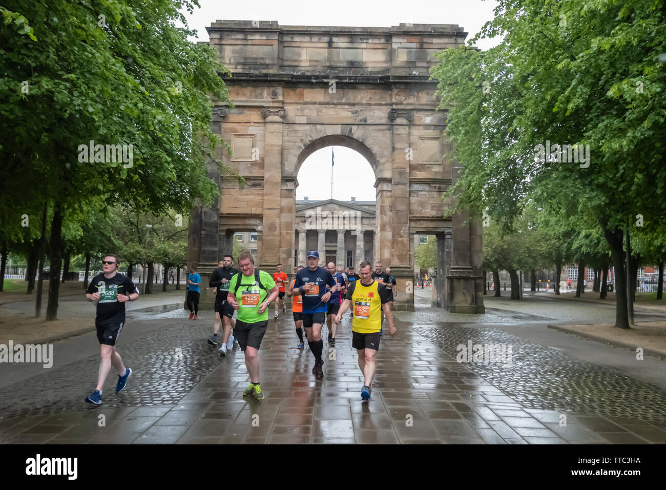 Glasgow, Scotland, UK. 16th June, 2019. Runners arrive at McLennan Arch in Glasgow Green during the Men's 10K Run which has been an annual event since 2004. Thousands of runners take to the streets of the city to get fit, fundraise, and raise awareness of men's health issues. The run coincides with Fathers Day and starts at the Riverside Museum and  finishes at George Square. Credit: Skully/Alamy Live News - Stock Image