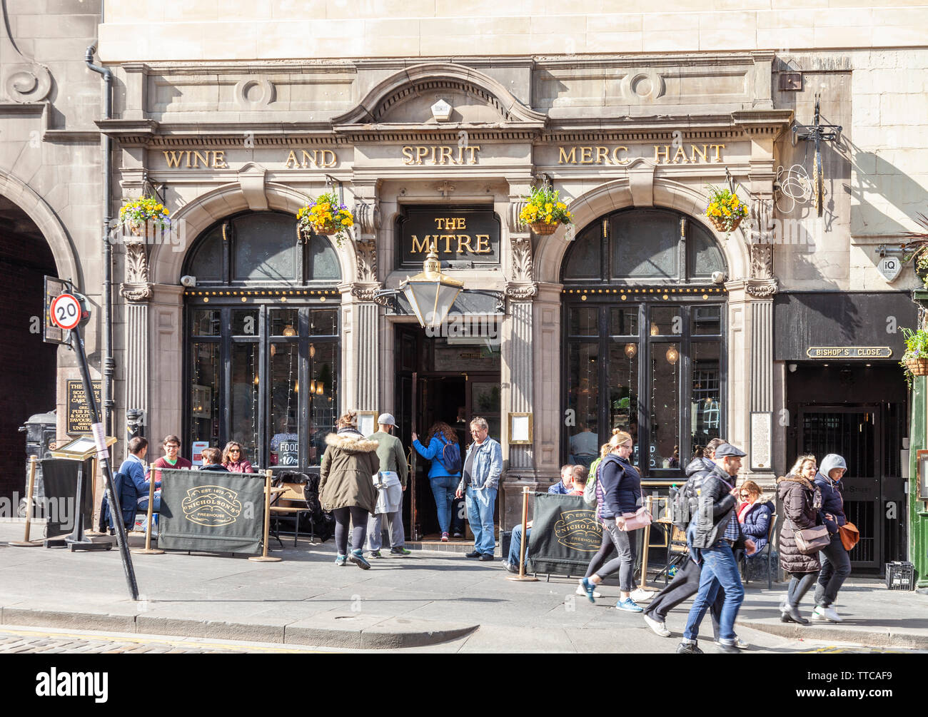 Cusomers outside and pedestrians passing the Mitre Bar, a city centre pub in the Royal Mile in the Old Town area of Edinburgh, Scotland, UK - Stock Image