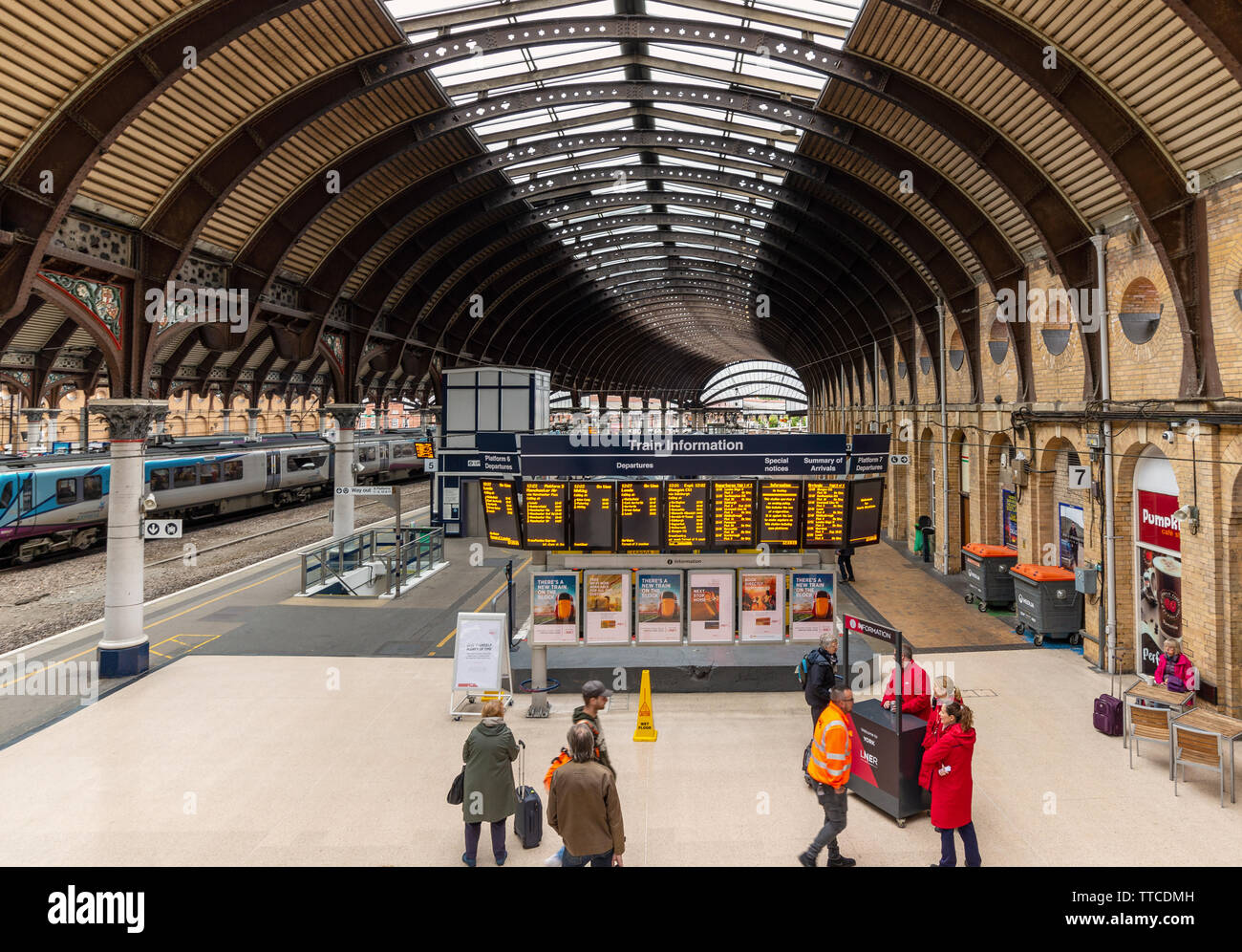 An electronic notice board at York Railway Station giving times of train departures and arrivals.  Passengers check times and a train waits to depart. - Stock Image