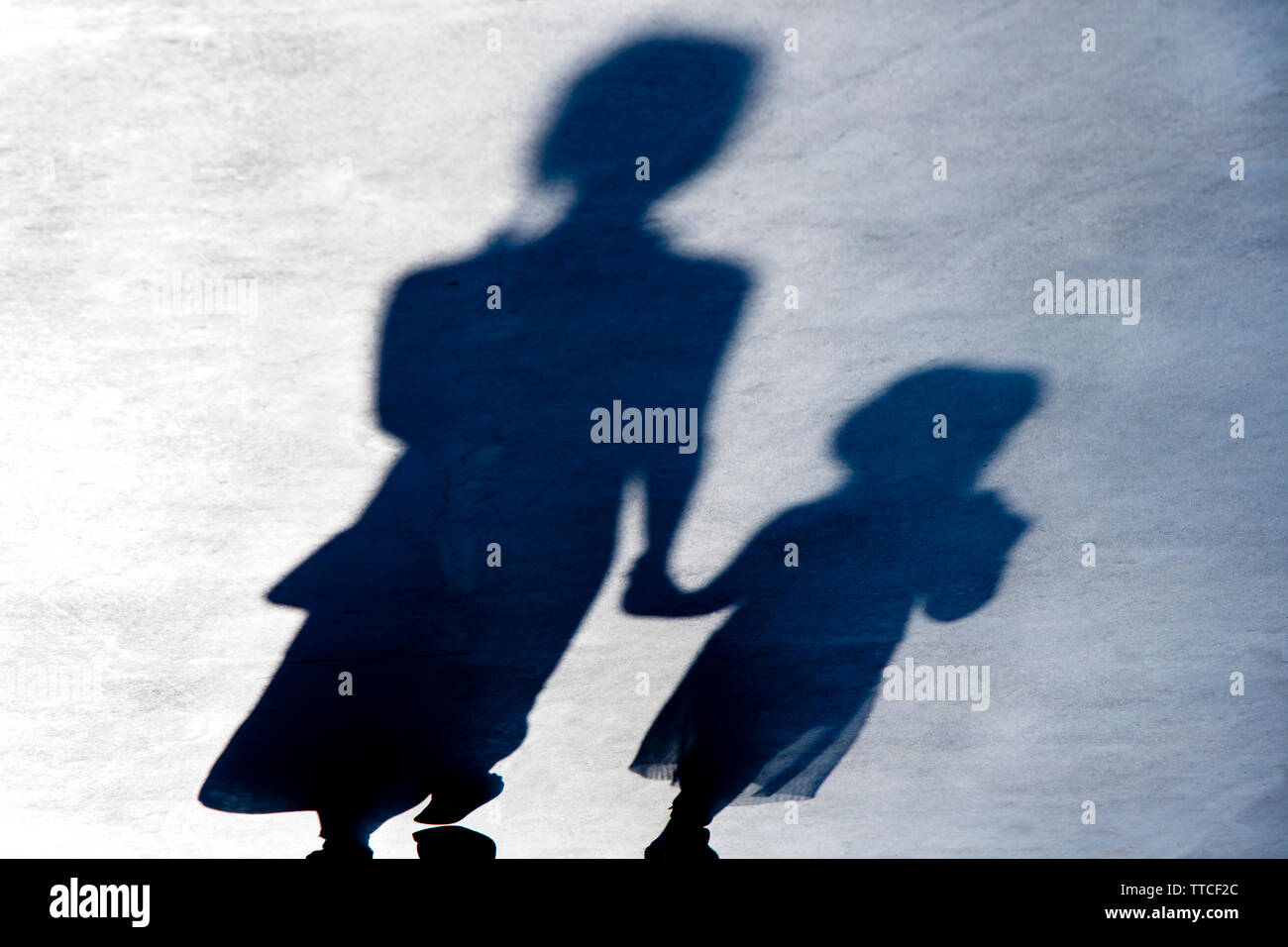 Blurry vintage shadows silhouettes of two female person walking  in black and white night - Stock Image