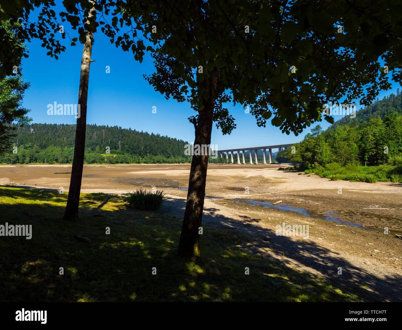 Dried lake-bed Bajer in Fuzine Croatia Spring 2019 highway bridge in background Stock Photo