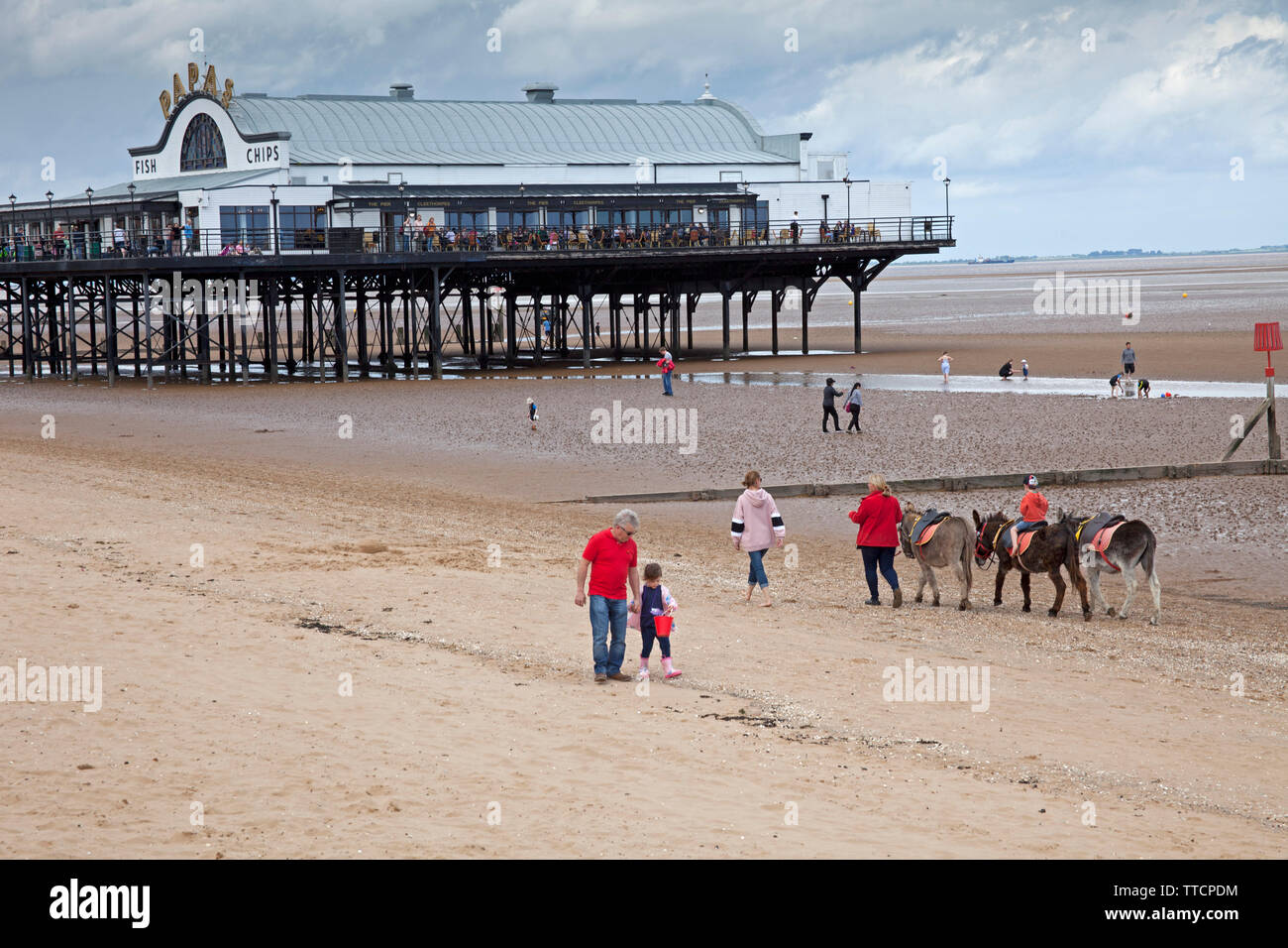 Cleethorpes, Lincolnshire, UK. 16th June 2019. UK weather. While northern parts of Lincolnshire suffer the remants of flooding, in Cleethorpes in north east Linconshire on Sunday afternoon families were enjoying the sun shine on Cleethorpes sandy beach with The Pier in the background, one little girl flying a kite with her family, others riding the donkeys and the next sheltering from a torrential downpour. Warm with 18 degrees. - Stock Image
