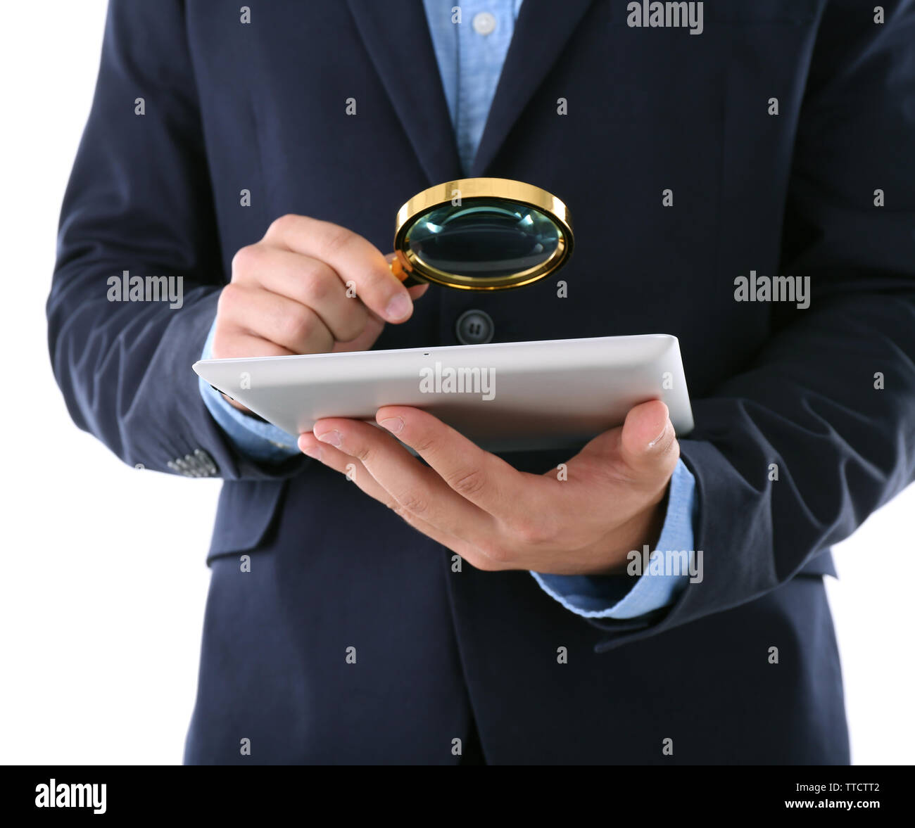 Businessman holding magnifying glass and digital tablet, isolated on white, searching and examining concept Stock Photo