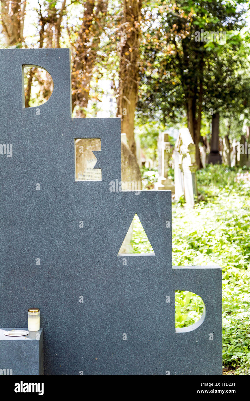 Humorous headstone saying 'Dead', Patrick Caulfield's grave at Highgate East Cemetery, London, UK Stock Photo