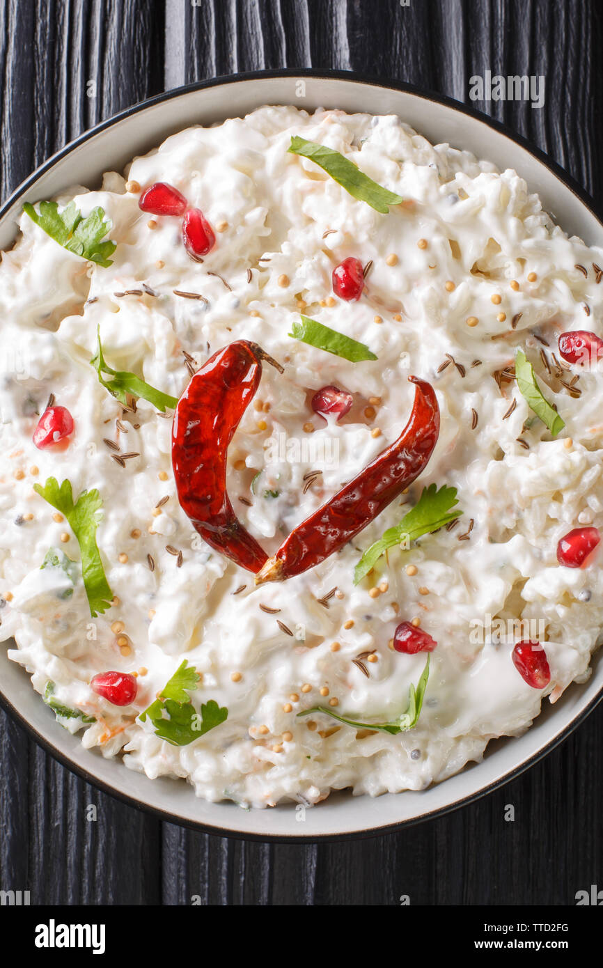 Indian Curd rice with carrots, pomegranate and with additional tempering of spices close-up in a plate on the table. Vertical top view from above Stock Photo
