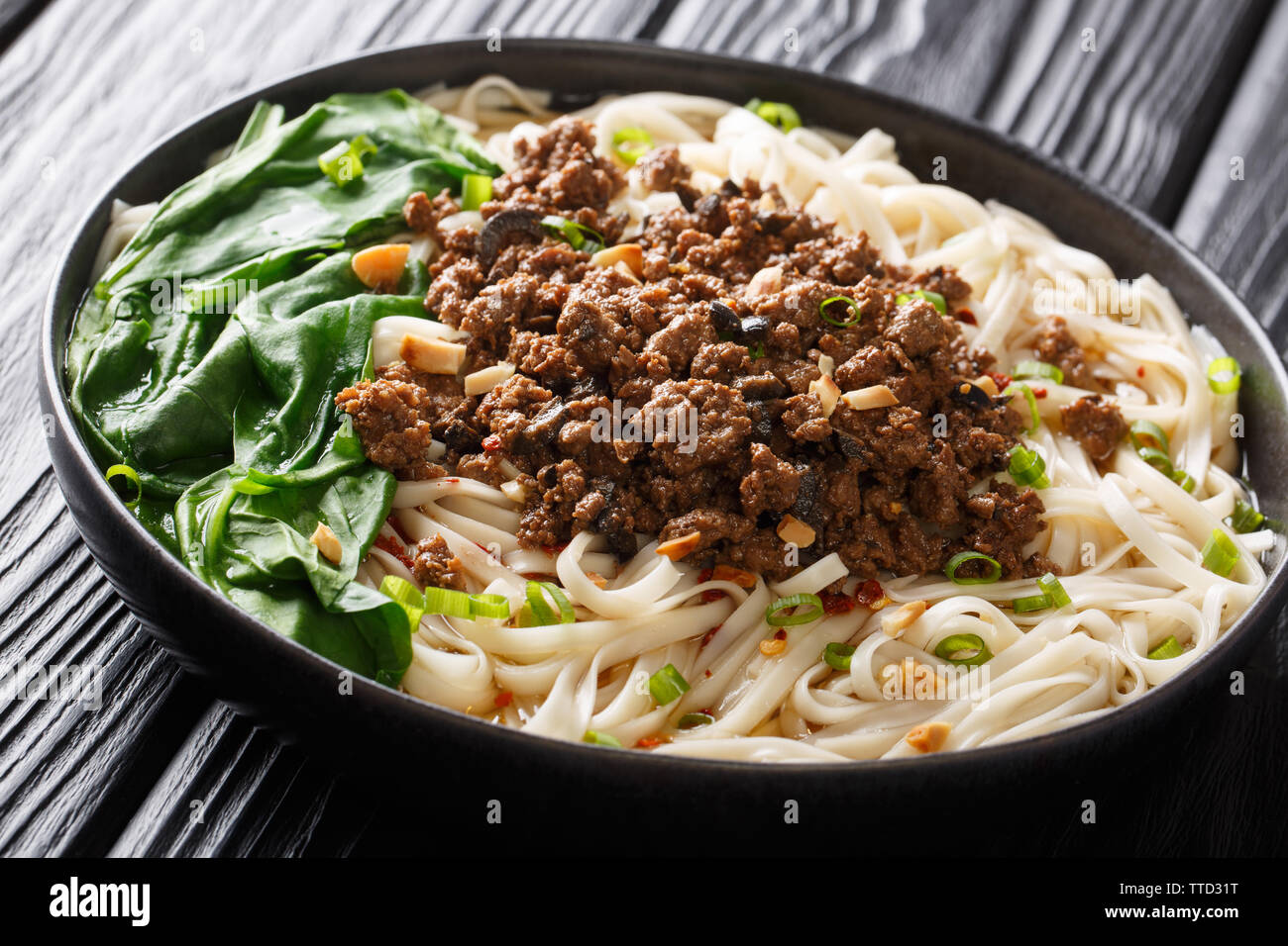 Traditional Chinese Sichuan Dan Dan Noodles with minced meat and greens in a plate on the table. horizontal Stock Photo