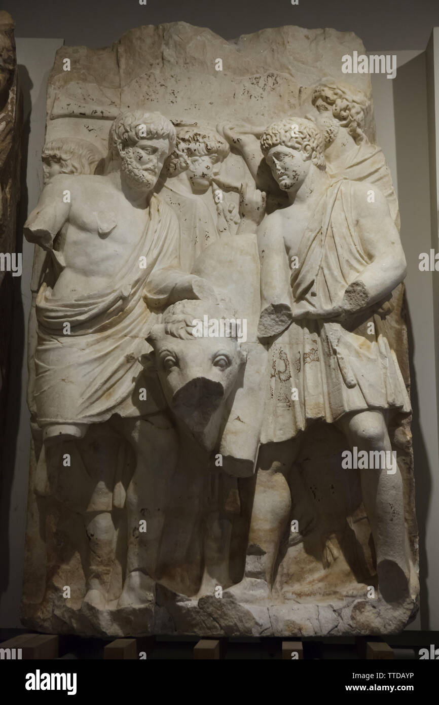 Sacrificial scene depicted in the marble relief from the Parthian Monument in Ephesus (now Selçuk, Turkey), now on display in the Ephesos Museum in Vienna, Austria. The Adoption ceremony on 25 February 138 AD, when Emperor Hadrian adopted his successor Antonius Pius, who in turn adopted his successors Marcus Aurelius and Lucius Verus is depicted in the Roman marble relieves dated from the 2nd century AD. Attendants with the sacrificial bull are depicted in the fragment. - Stock Image