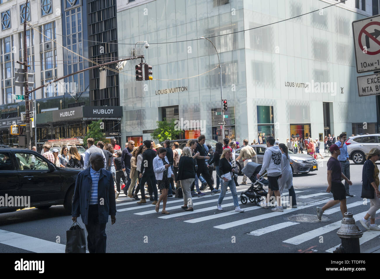 Pedestrians cross the always busy corner of 5th Avenue and 57th Street in midtown Manhattan. - Stock Image