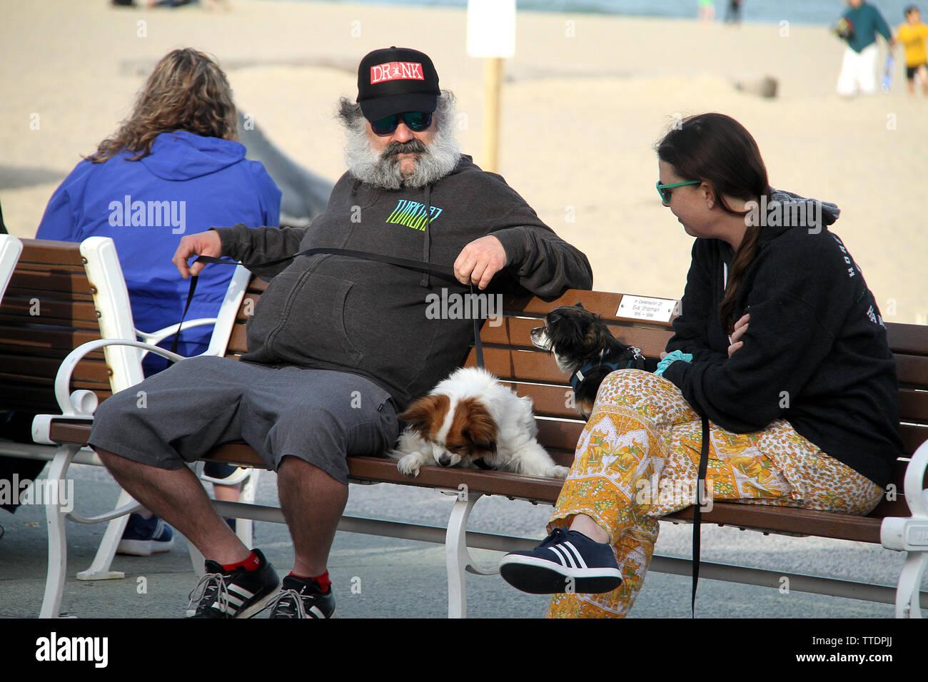 Owners of small dogs sitting on a bench on the boardwalk. Ocean City, MD, USA. - Stock Image
