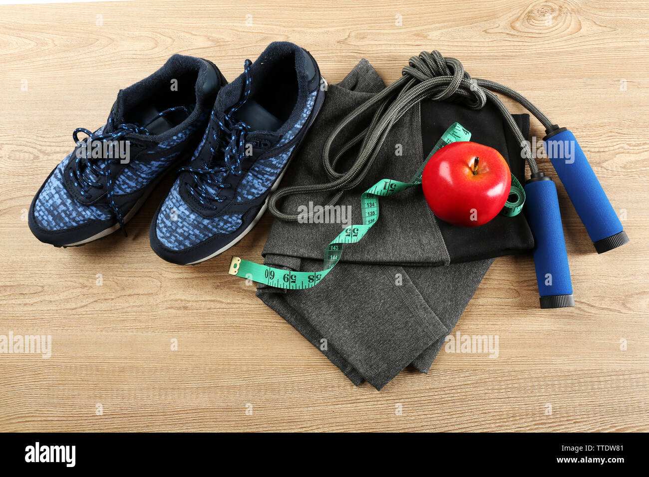 Sport shoes, clothes, equipment and smart phone with headphones on light background - Stock Image