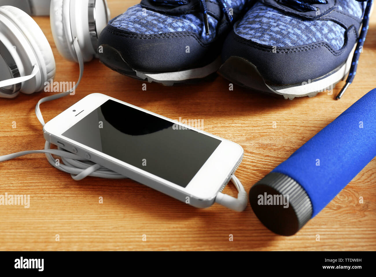 Sport shoes, equipment and smart phone with headphones on light background - Stock Image