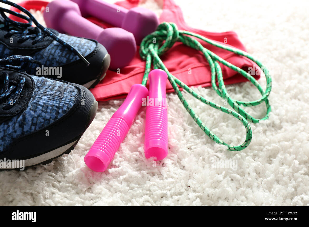 Sport clothes and equipment on white carpet background - Stock Image