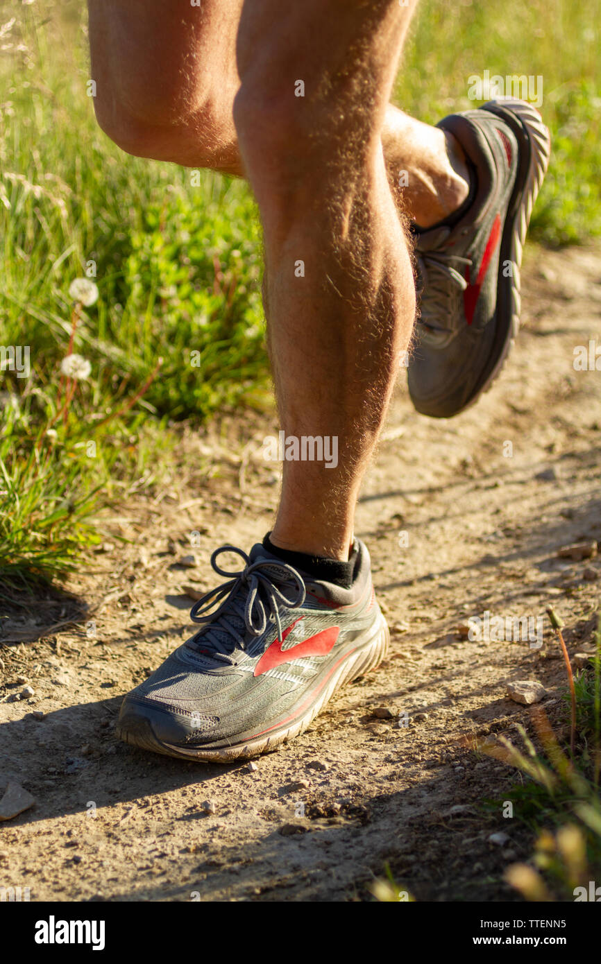 Man with muscular legs wearing Brooks trail running shoes isolated with a natural background, early morning light. - Stock Image