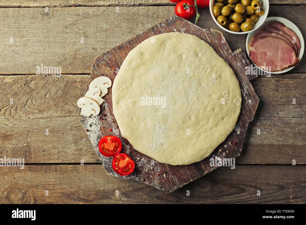 Fresh dough prepared for pizza with tomatoes and sliced mushrooms on a wooden board, close up - Stock Image