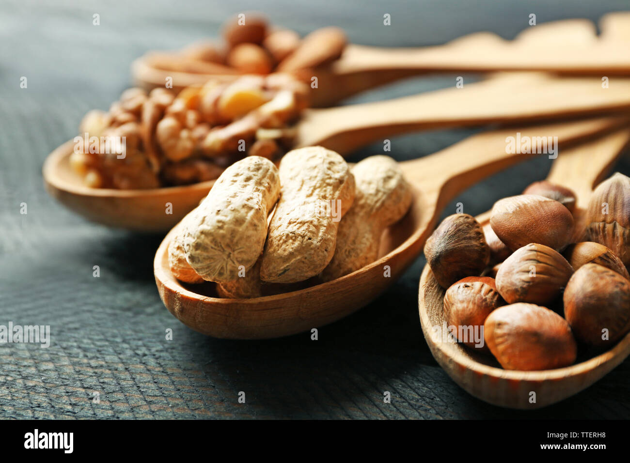Spoons with walnuts, pistachios, almonds, acorns and peanuts, on grey wooden background Stock Photo