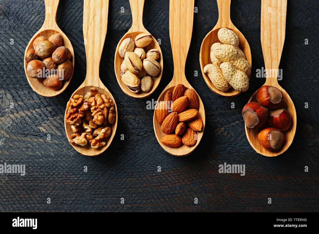 Spoons with hazelnuts, walnuts, pistachios, almonds, acorns and peanuts, on grey wooden background Stock Photo