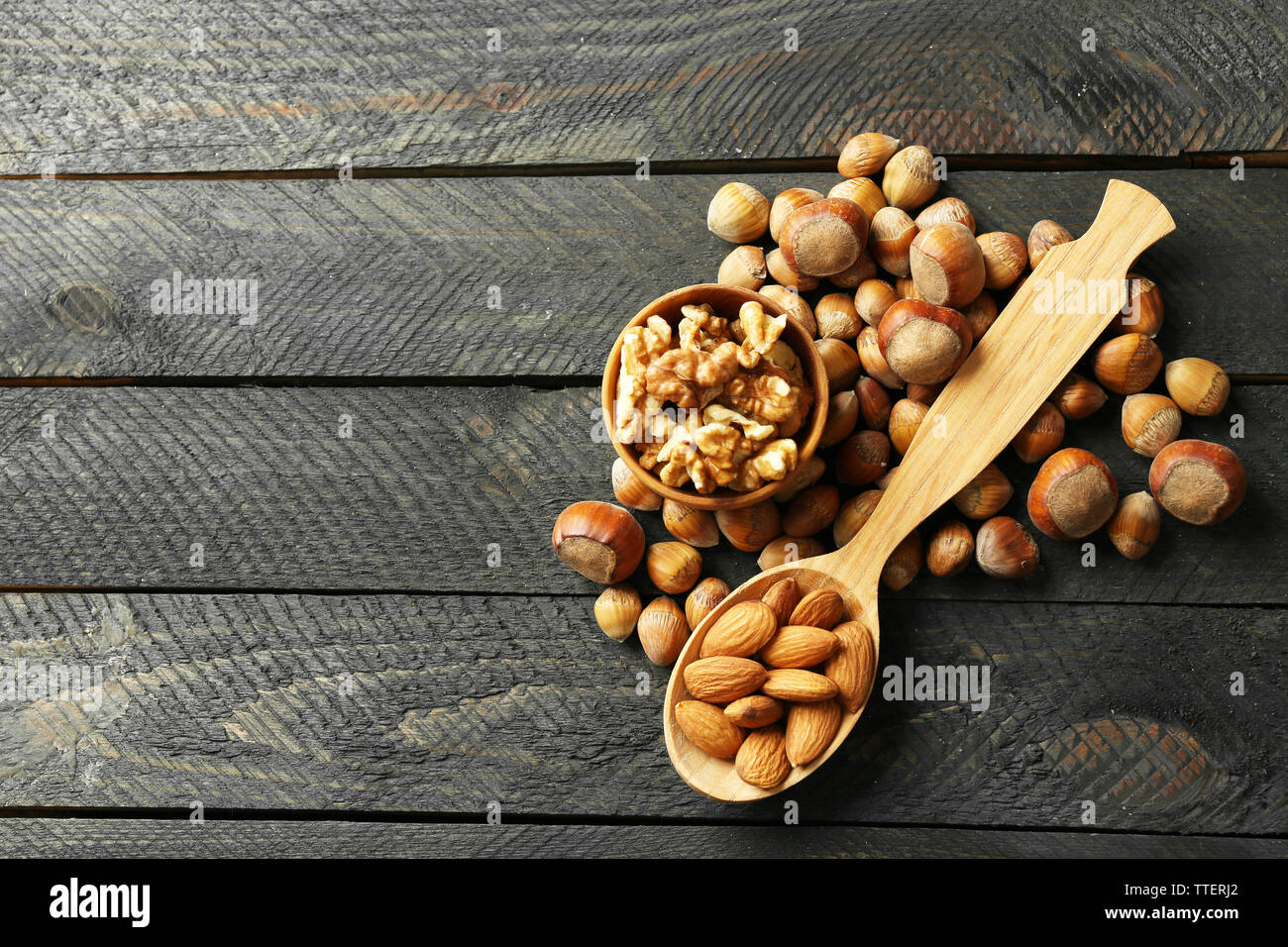 A wooden spoon, a bowl, hazelnuts, walnuts, almonds and acorns on the wooden table Stock Photo