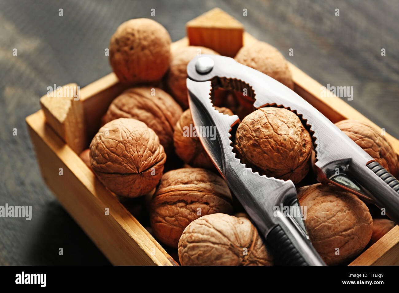 A box of walnuts and nutcracker on wooden background Stock Photo