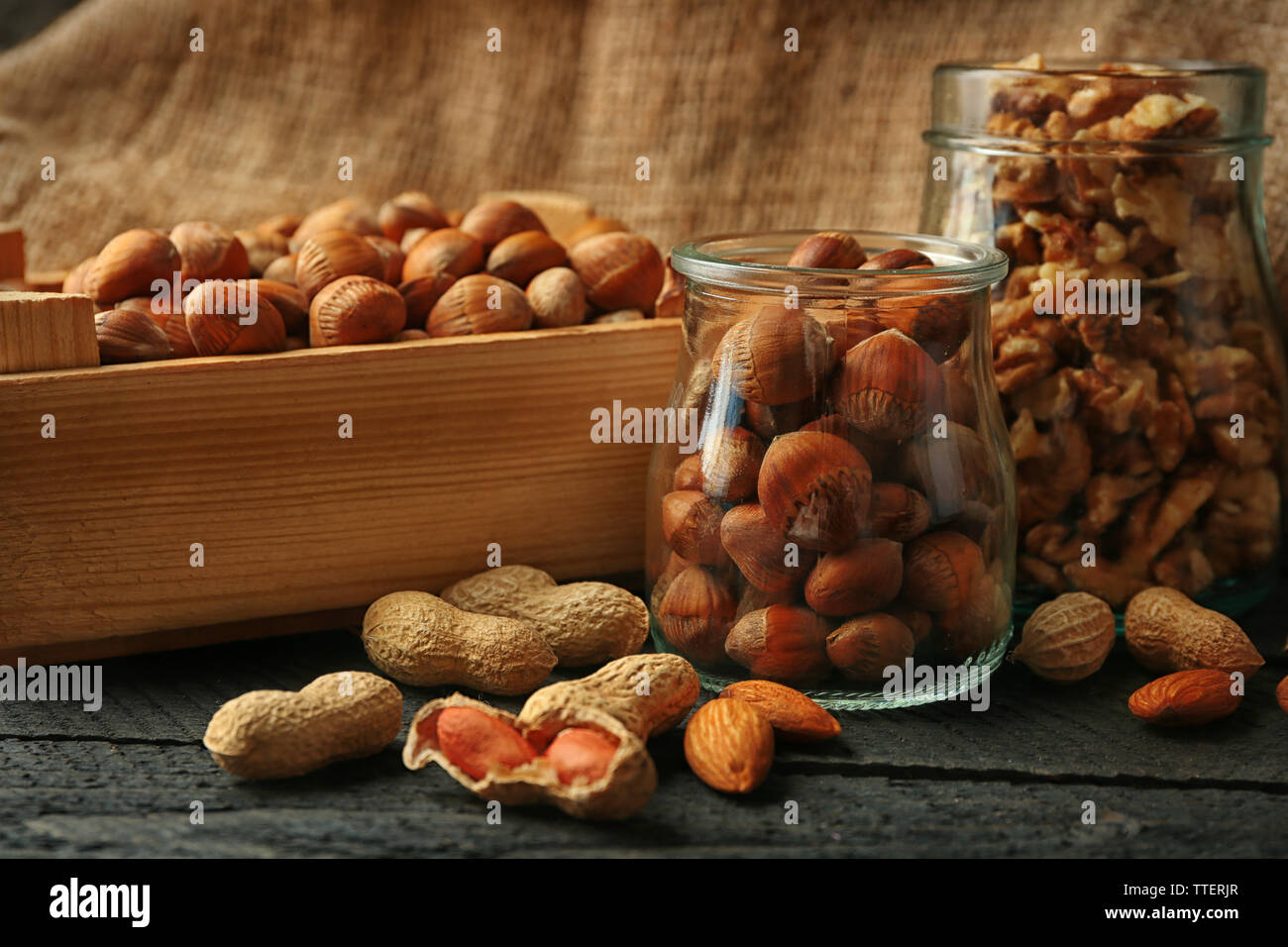 Mix of nuts in the glass jars and wooden box, on the table Stock Photo