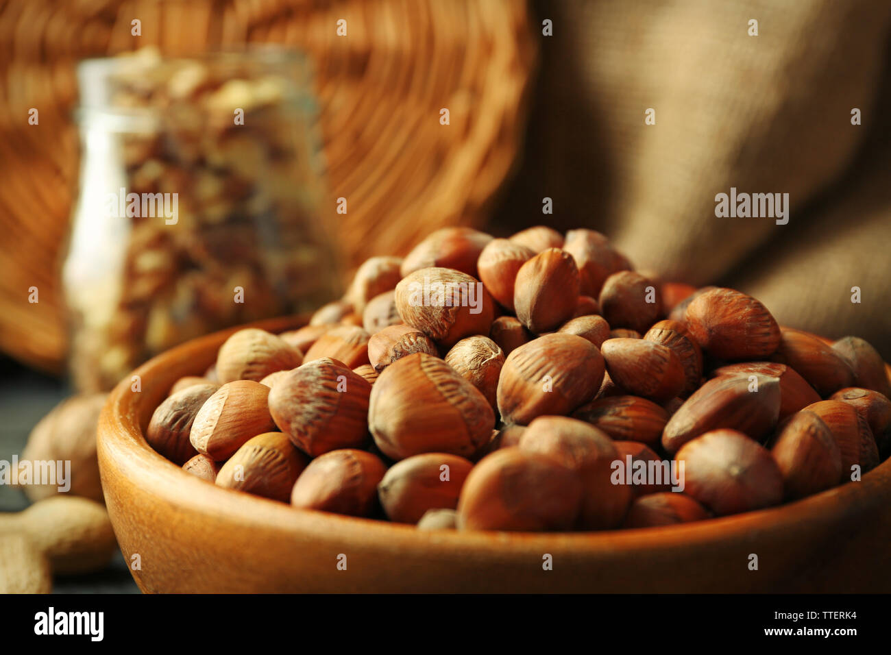 Hazelnuts, walnuts, peanuts in the bowl and glass jar on the table, close-up Stock Photo