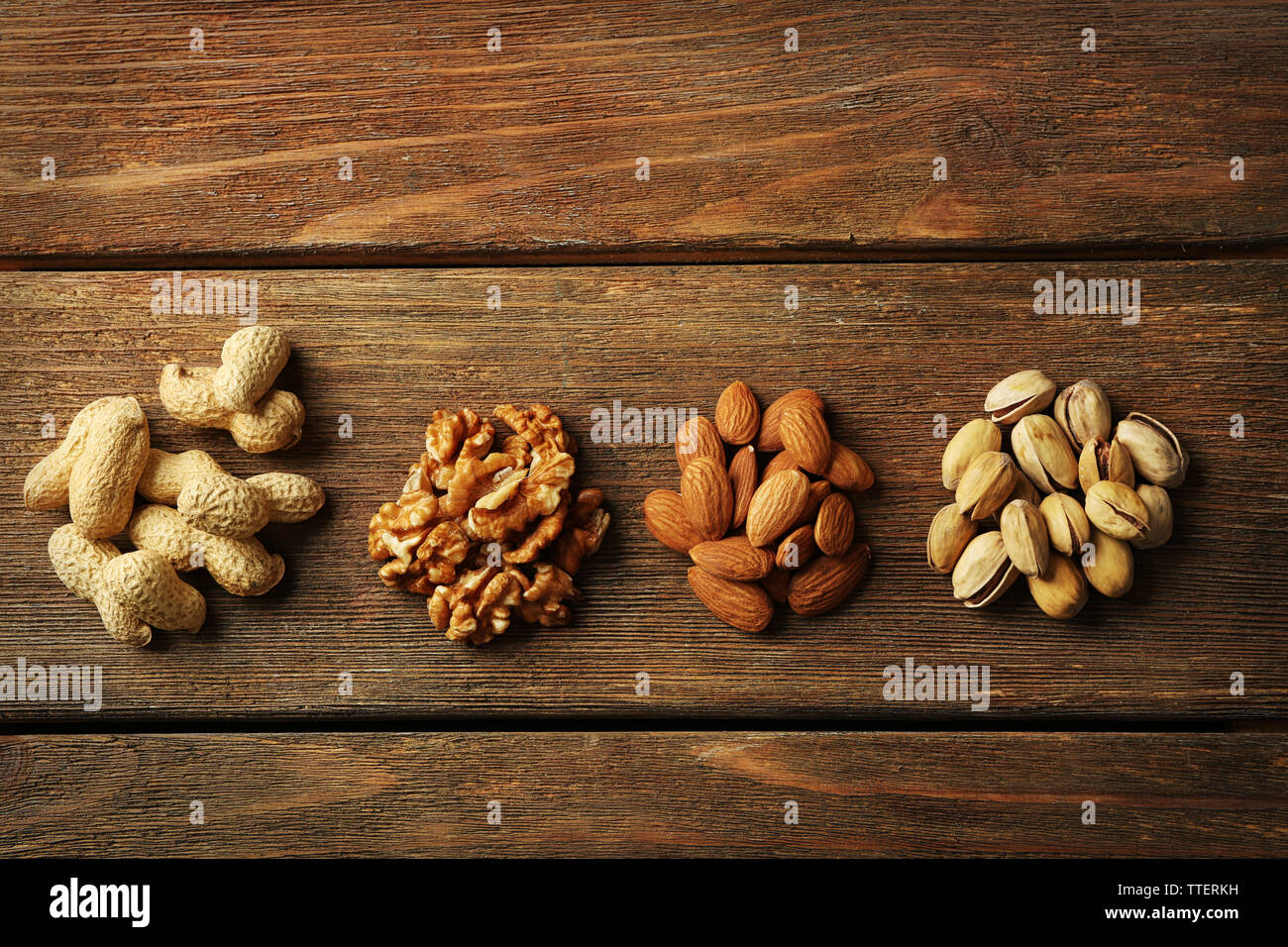 Four piles of pistachios, walnut kernel, almonds and peanuts on the wooden table Stock Photo