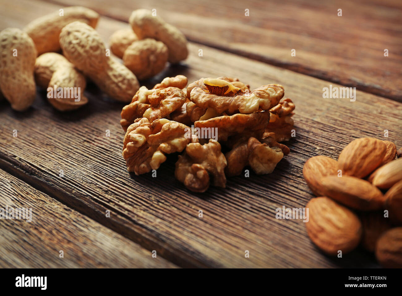 Peanuts, walnut kernel and almonds on the wooden table, close-up Stock Photo