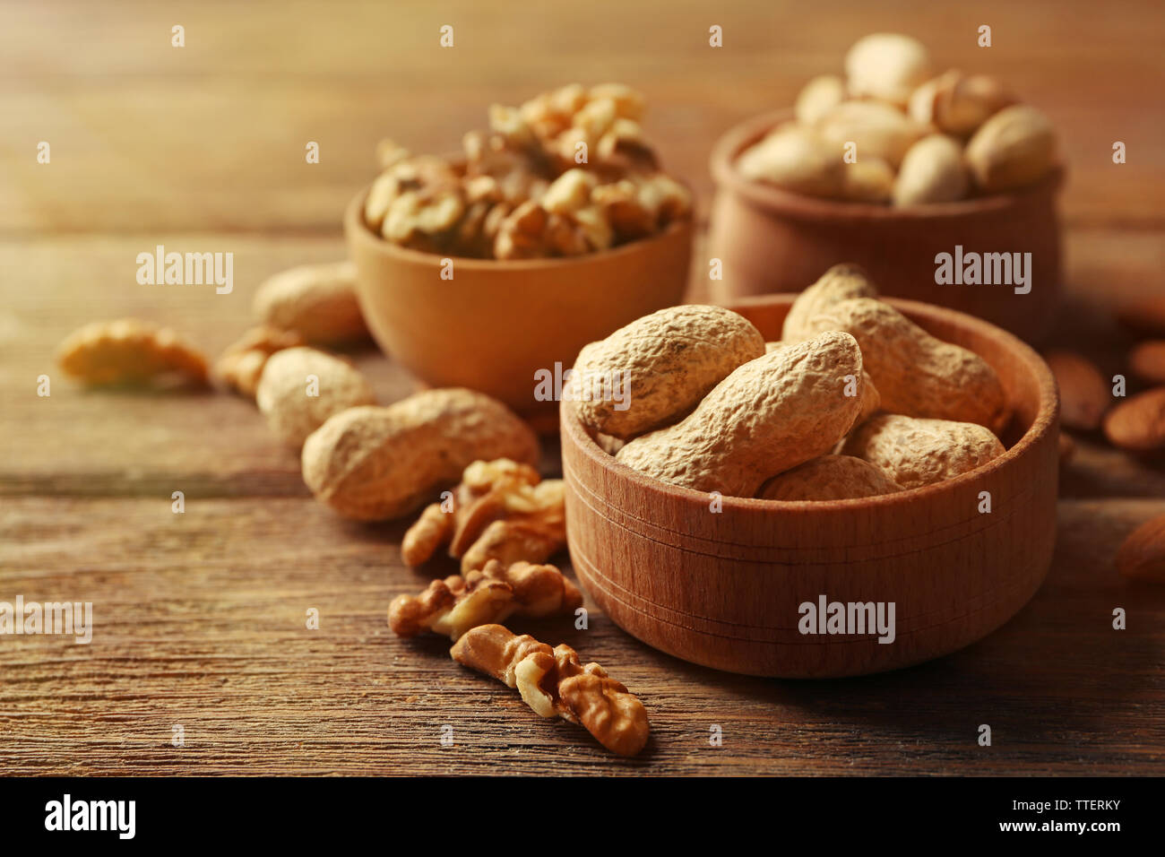 Pistachios, almonds, peanuts and walnut kernels in the wooden bowls on the table, close-up Stock Photo
