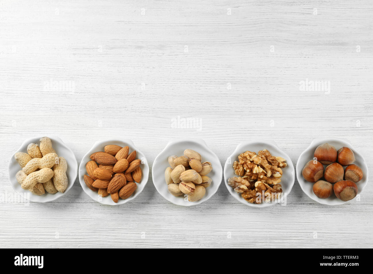 Pistachios, almonds, peanuts, walnut kernels and hazelnuts in the bowls on white wooden table Stock Photo
