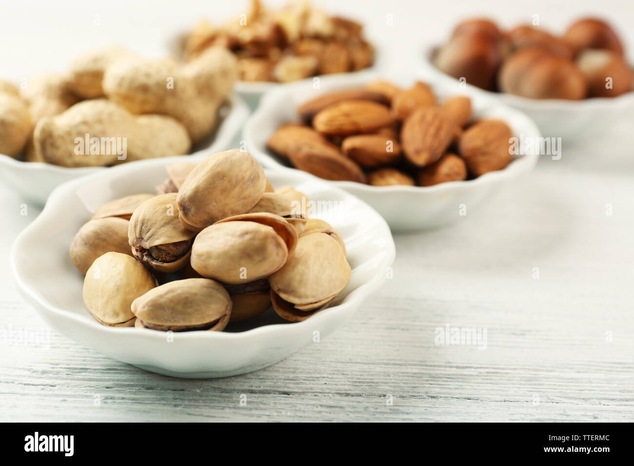 Pistachios, almonds, peanuts, walnut kernels and hazelnuts in the bowls on white wooden table, close-up Stock Photo