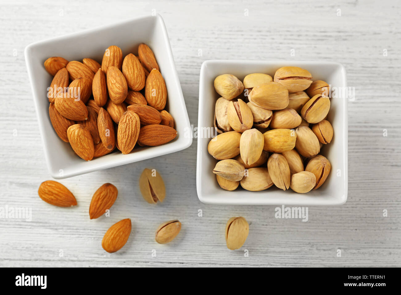 Pistachios and almonds in the bowls on white wooden background Stock Photo
