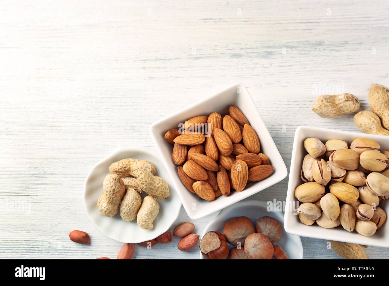 Pistachios, almonds, hazelnuts, peanuts and walnut kernels in the ceramic bowls, on white wooden backgrounds Stock Photo