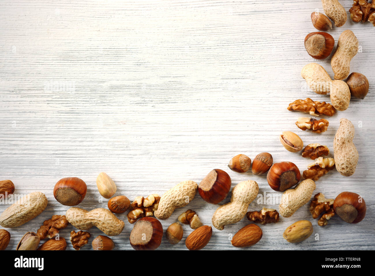 Corner made with mix of nuts on the white wooden table Stock Photo