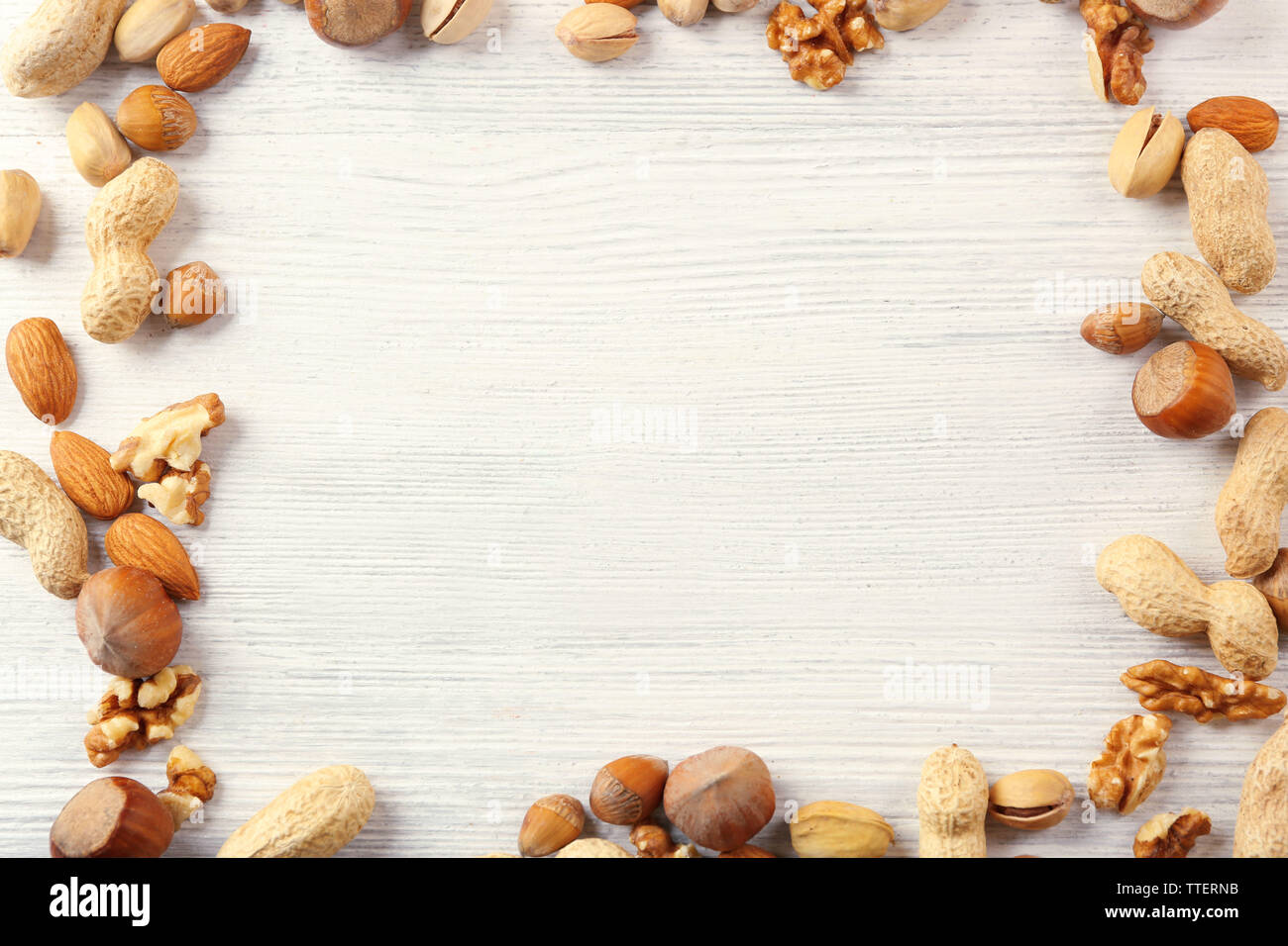 Frame made with mix of nuts on the white wooden table Stock Photo