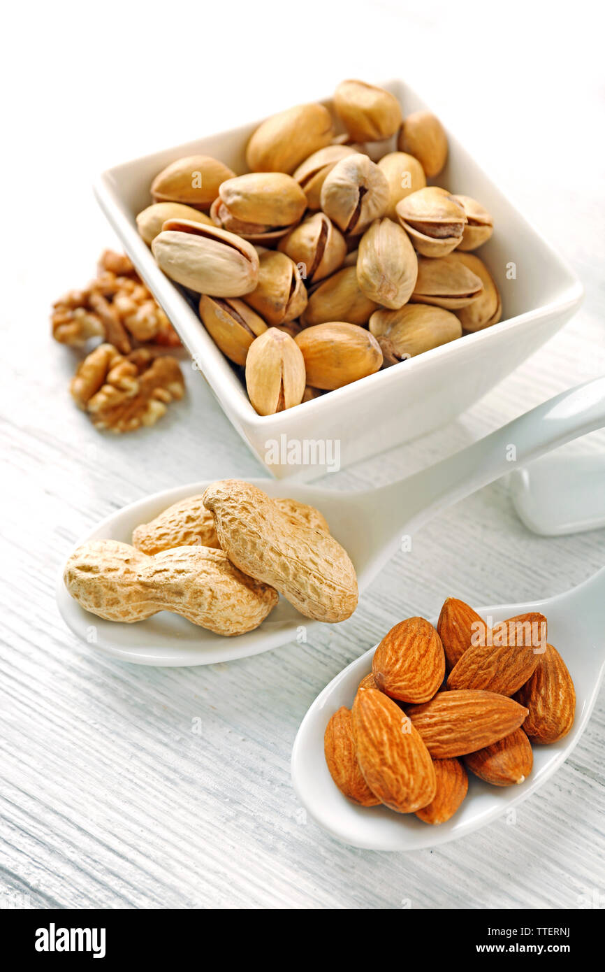 Pistachios, almonds, peanuts and walnut kernels in the ceramic bowl and spoons, on white wooden background Stock Photo