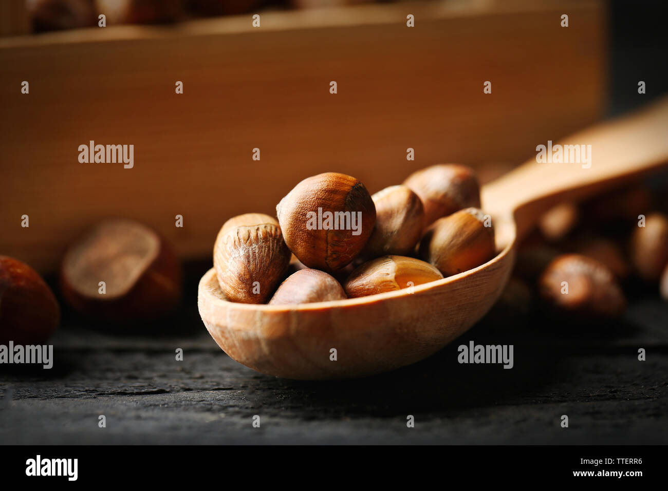 Hazelnuts in wooden box and spoon on the table, close-up Stock Photo